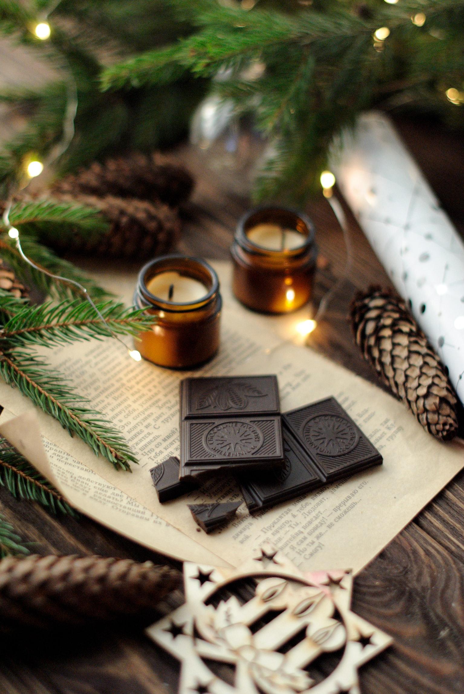 Branche de sapin verte et lumières lumineuses, chocolat noir, bougies souhaiter un joyeux noel, la magie des fêtes avec une belle carte