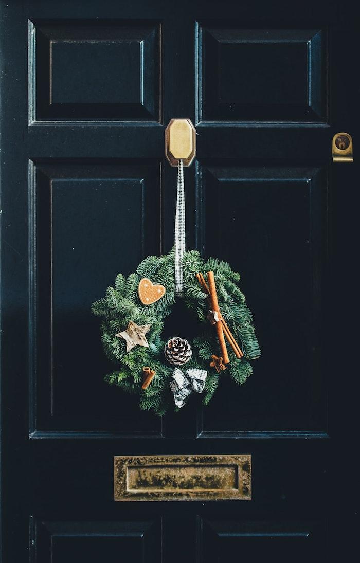 Porte d'entrée noire avec décoration couronne de pins, image joyeux noël, inspiration image pere noel à dessiner