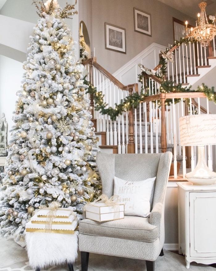 modèle gros arbre de Noël artificiel aux branches blanches décoré avec guirlandes et ornements en argent et or