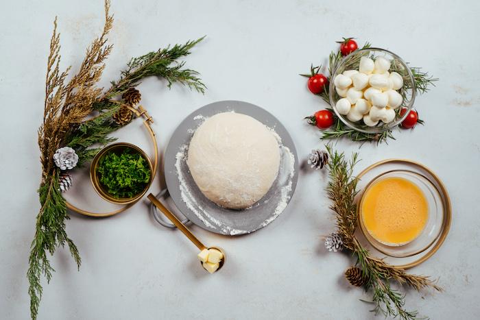 ingredients necessaires pour faire un pain de noel, pâte à pizza, mini boules de mozzarella, oeuf battu, coriandre haché, beurre ramolli