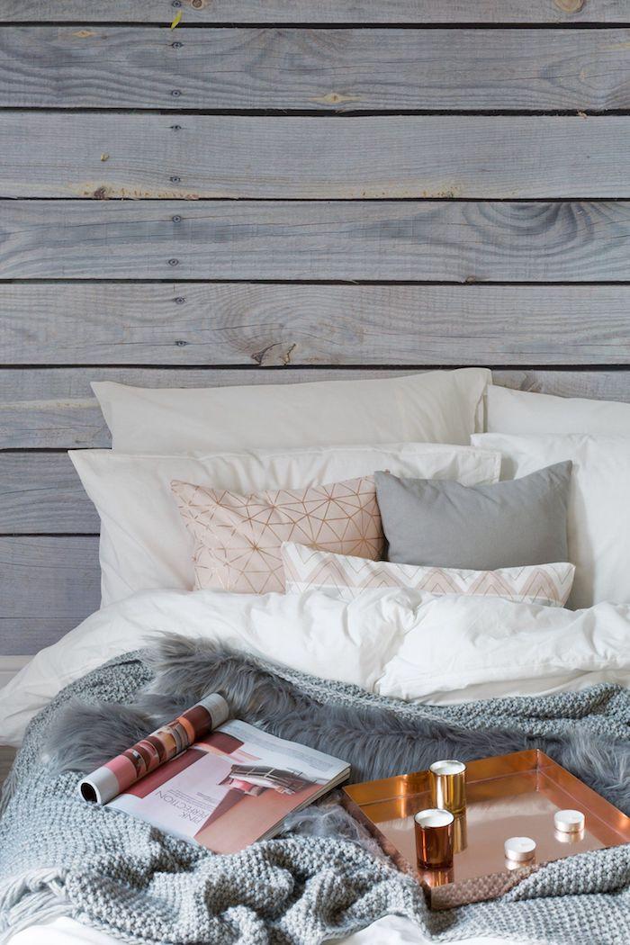 Coin lit confortable, association de couleur avec le gris, chambre grise, magazine à lire au lit, table avec bougies cuivre
