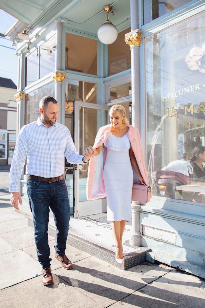 Belle femme bien habillée en robe blanche moulante et manteau rose accessoirisé de sac à main rose à la meme couleur, robe de reveillon, devenir une femme élégante