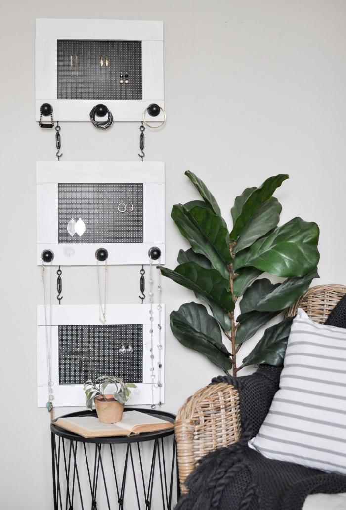 design intérieur minimaliste, idée porte bijoux mural en bois blanc avec grillage et crochets, coin lecture avec chaise rotin et table café