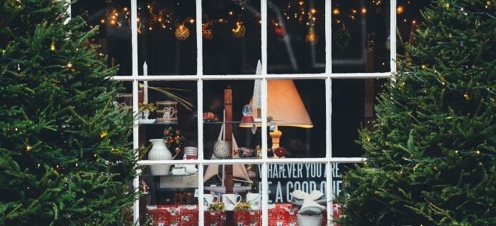 idée wallpaper pour ordinateur sur thème décoration de noel, photo de sapins naturels devant une fenêtre décorée en rouge et or boules