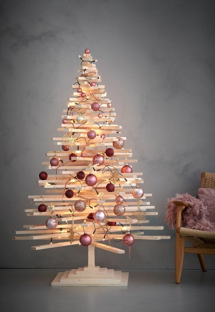idée de deco de noel a faire soi meme, modèle de sapin minimaliste fabriqué avec goujons de bois et décorés avec boules en nuances de rose