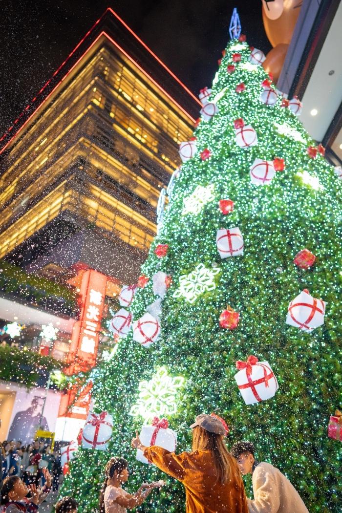 belle image de noel pour fond d'écran iphone, célébration fête de Noel au centre-ville devant un géant sapin décoré en vert et rouge