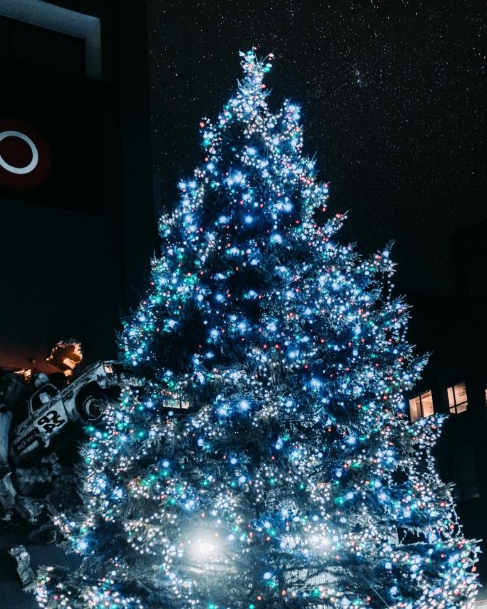 image joyeux noel 2019, wallpaper Noel pour ordinateur avec photo d'un gros sapin décoré en guirlande lumineuse bleue