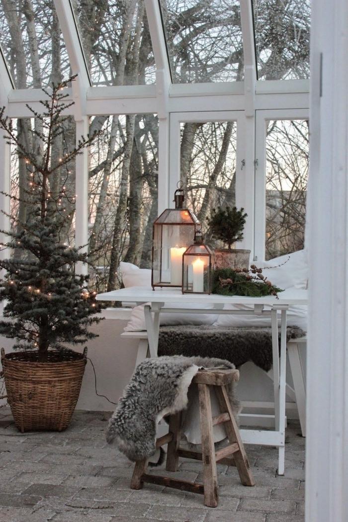 ambiance cocooning dans une pièce aux grandes fenêtres aménagée avec meubles en bois, idée deco noel nature avec arbre de Noël naturel