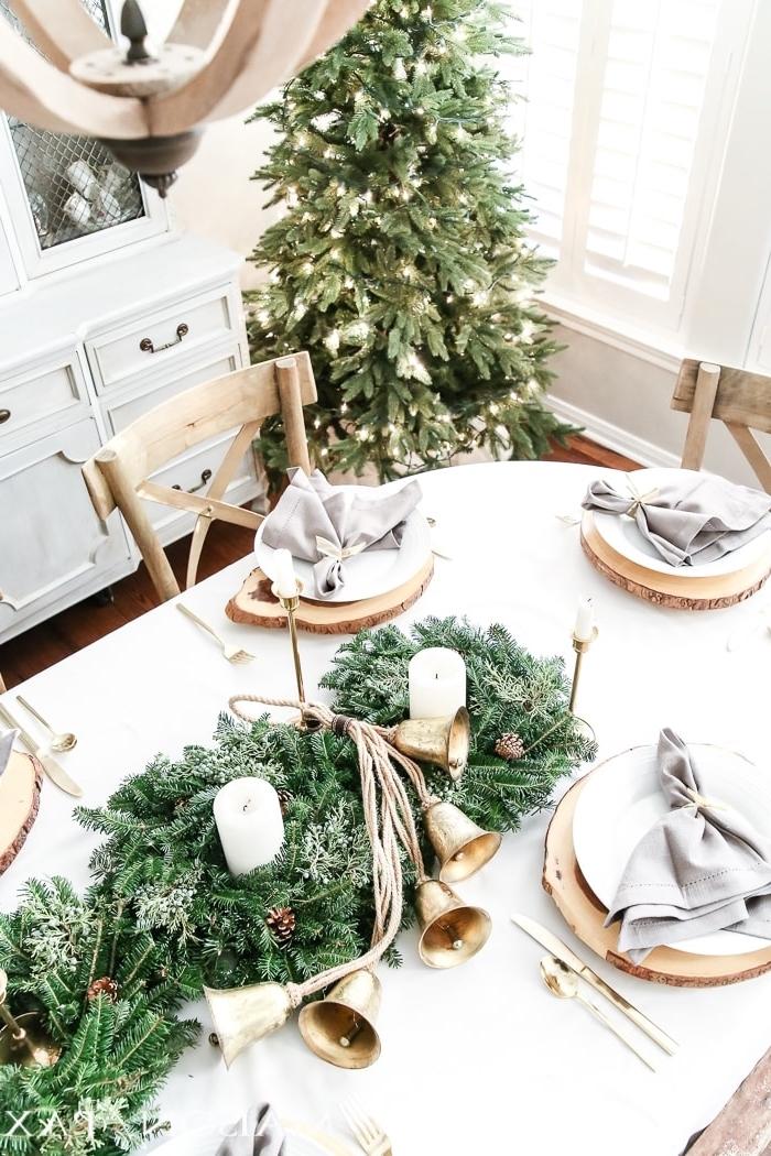 idée de deco de table de noel en blanc et bois avec centre de table DIY en gris de verdures artificielles et bougies
