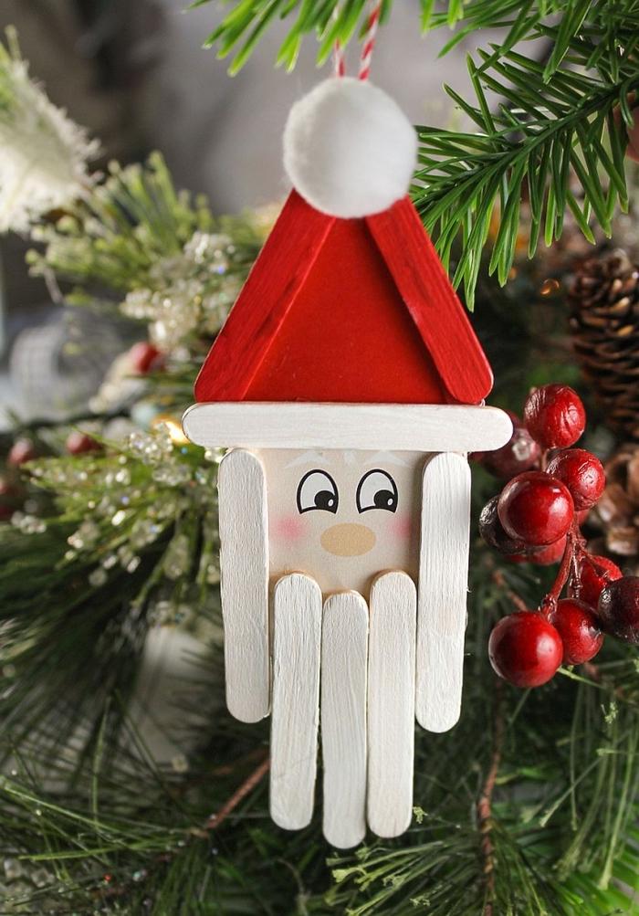 modèle d'ornement pour sapin de Noël fait maison avec rondelle bois et bâtonnets de glace en forme de tête de père noel