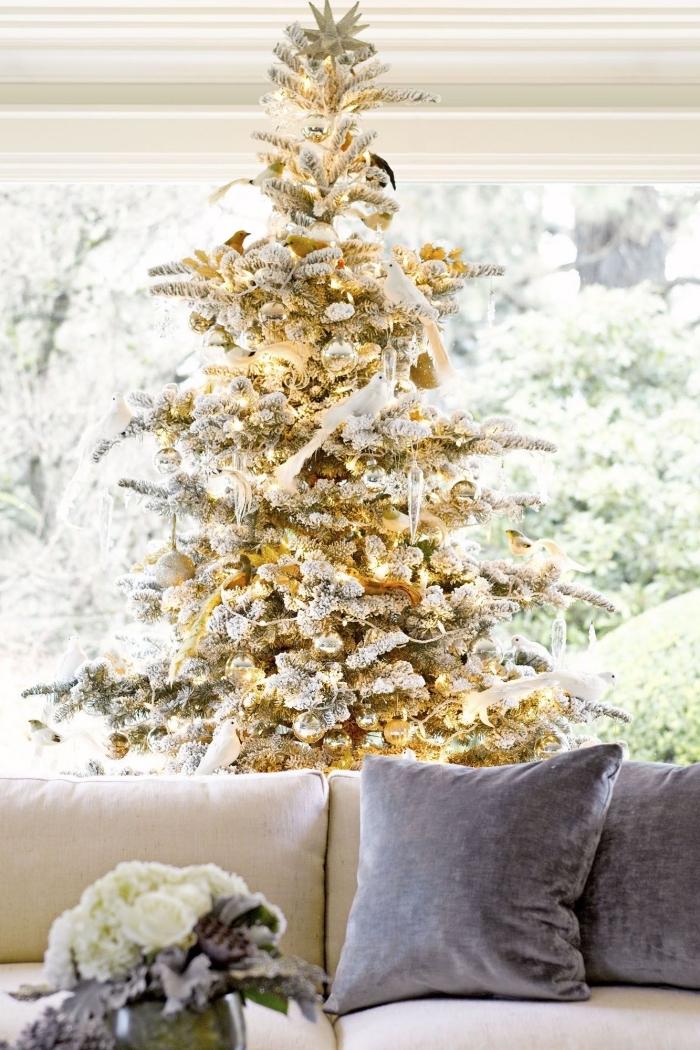 design intérieur tendance noel 2019, salon avec grande fenêtre aménagé avec canapé en tissu beige et arbre de Noël en or et argent