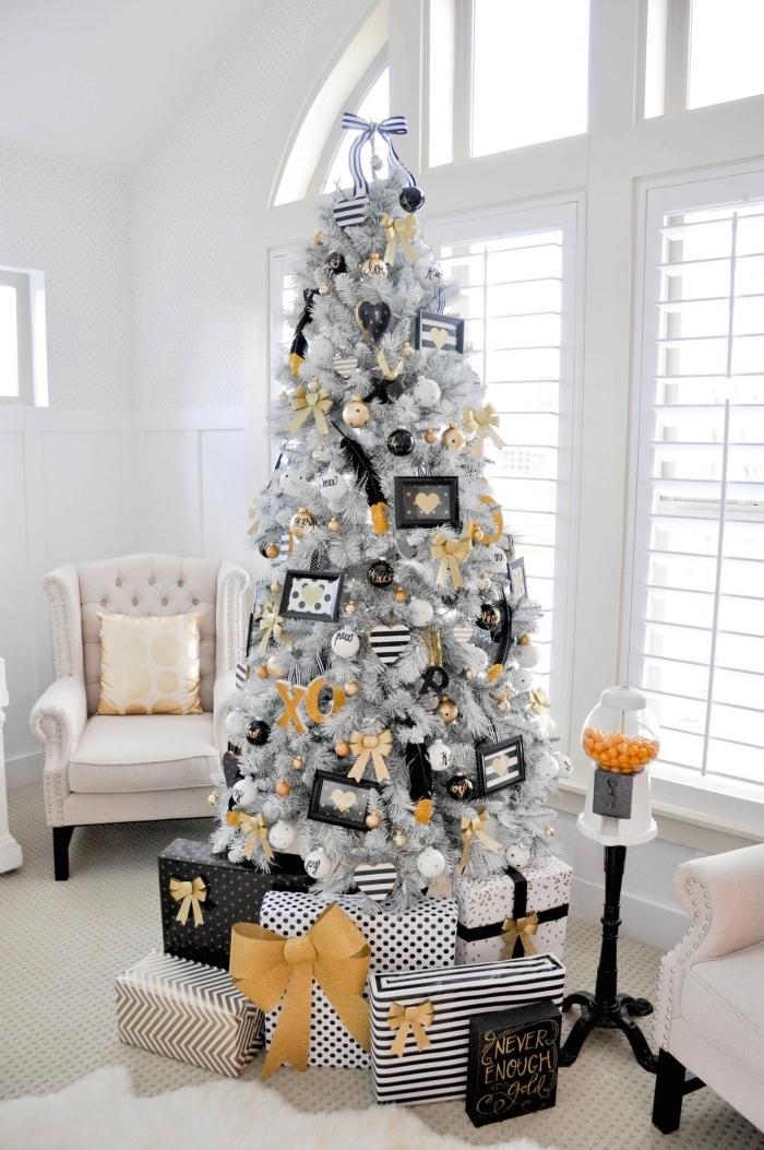 modèle de sapin de noel original aux branches blanches décoré en orange et noir, idée décor stylé dans un salon blanc à plafond cathédrale