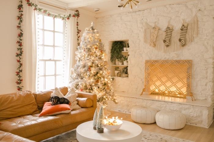 ambiance cocooning dans un salon blanc avec plancher bois et meuble en cuir camel, déco de Noël originale avec sapin de Noel blanc et gris