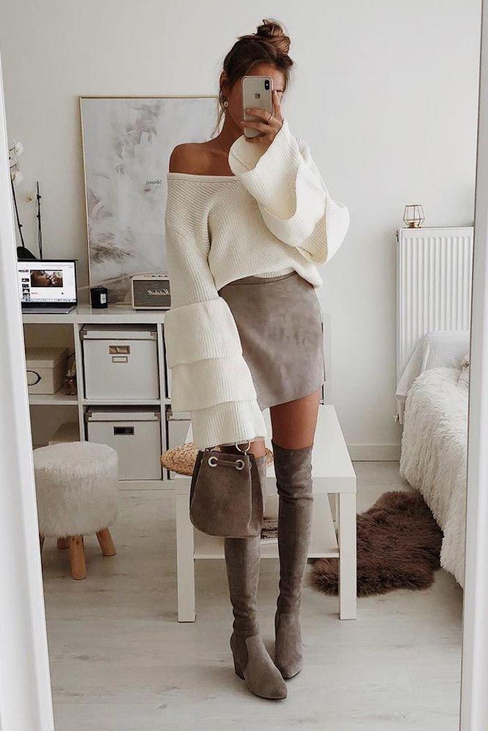 Selfie dans le miroir de femme bien habillée en bottes cuissardes en velours, mini-jupe et blanc pull avec manches évasées