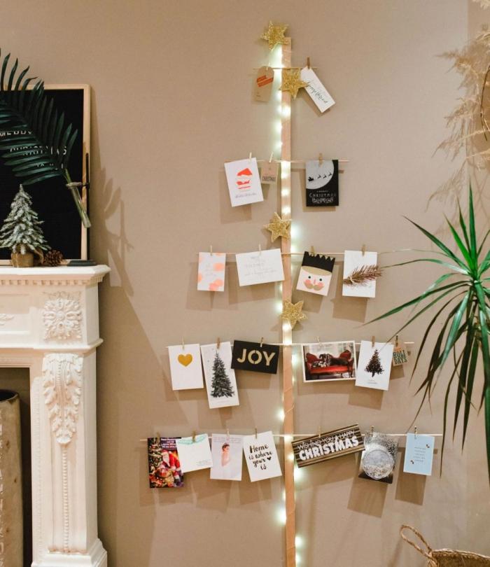 décoration sapin de noel tendance DIY, modèle d'arbre de Noël fait main avec bâtonnets de bois et décoré de cartes postales
