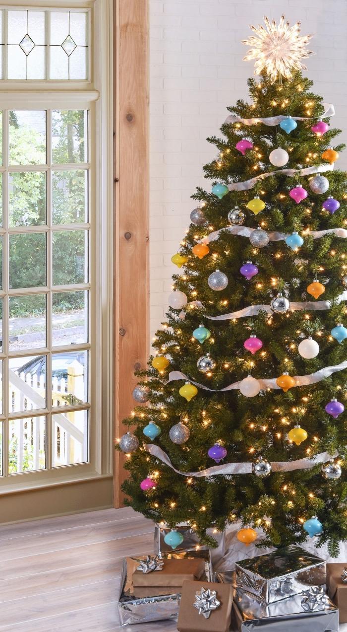 quel thème de décoration pour un sapin de Noël original, image sapin de noel naturel décoré avec ruban argent et boules différentes couleurs
