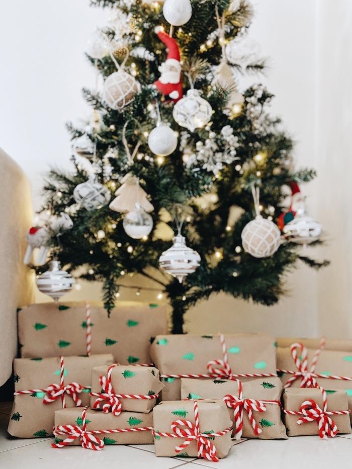 photo sapin de noel décoré en blanc et or avec figurines père Noël, image de pere noel en forme d'ornement de sapin