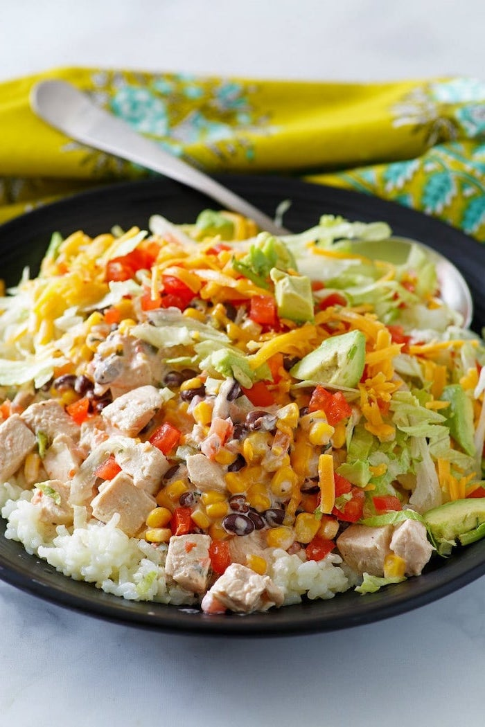 bol taco maison remplie de légumes, maïs, haricots noirs, fromage, avocat avec des bouchées de poulet le tout servi sur canapé de riz