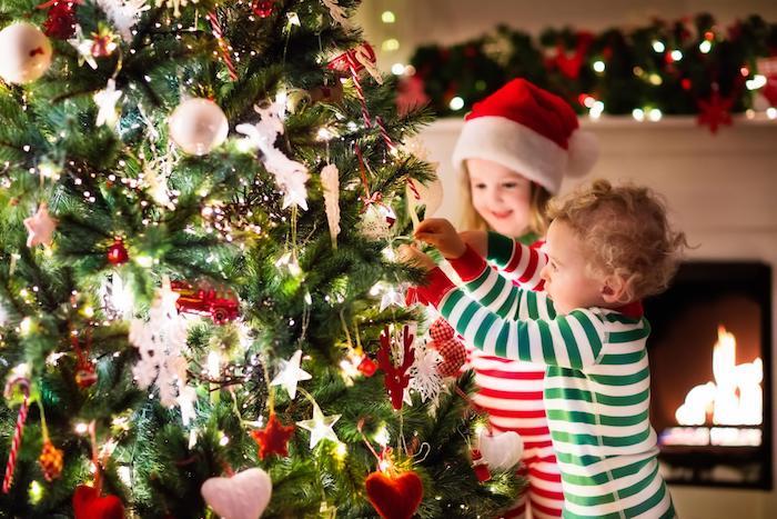 Enfants qui mettent la décoration de l'arbre de noel, guirlande lumineuse et boules de noel, image de pere noel, souhaiter un joyeux noel a ses amis