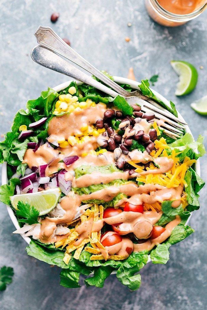 salade composée originale constituée de laitue, oignons, tomates cerise, harictos noirs, maïs avec de la sauce