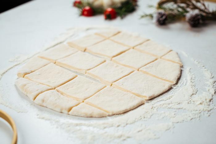 couper des carrés de pâte à pizza avec couteau roulette à pâte, etape pour faire aperitif noel facile