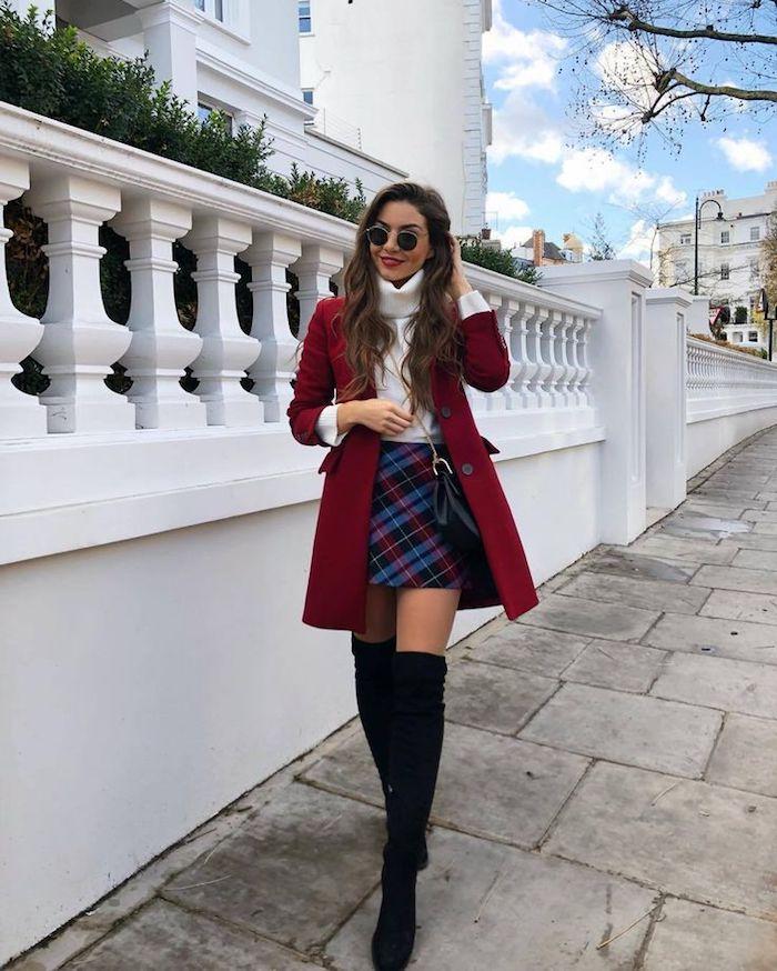 Femme tenue avec cuissardes à talon, manteau rouge longue, mini-jupe carrée et pull blanc à col roulé, lunettes de soleil rondes
