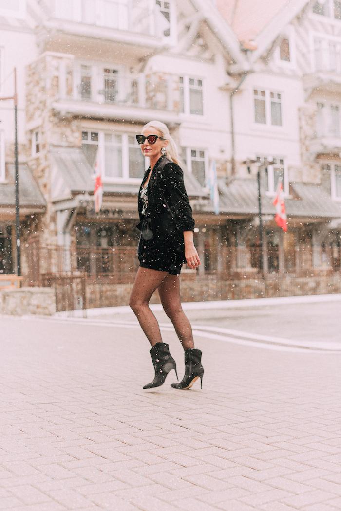 Noire et argentée robe courte manche longue, moderne robe pour noel accessoirisé de bottines à talon haut pointus, femme blonde cheveux longs et lunettes de soleil