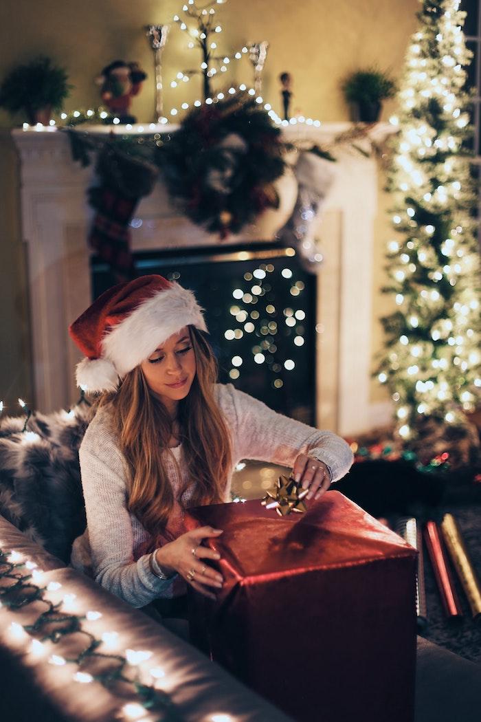 Femme ouvrant un cadeau, sapin de noel décoré de guirlandes lumineuses, image joyeuses fêtes, photo joyeux noel desktop