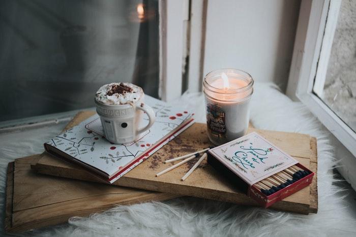 Bougie aromatique et livre devant le fenetre, souhaiter un joyeux noel, fond d écran image de noel