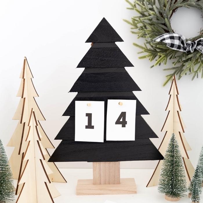 modèle de calendrier de l'avent DIY à réaliser avec sapin de noel en bois repeint en noir mat et des morceaux de papier numérotés