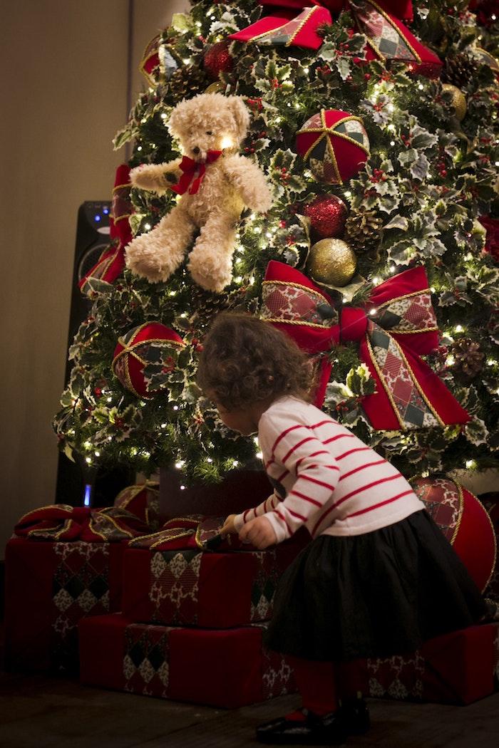 Sapin de Noël décoré joliment, enfant qui veut ouvrir les cadeaux, image pere noel, la fête de noël image stylé