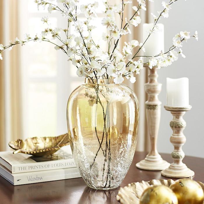 Branche fleurie dans bonbonne dame jeanne jaune, déco tourie style vintage cool, bougies sur haute chaise