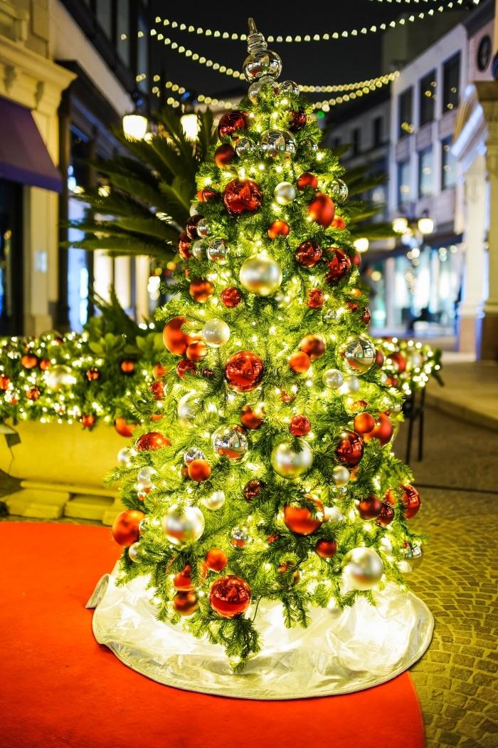 exemple de sapin rouge et blanc extérieur sur une rue pavée avec décoration en guirlandes lumineuses d'extérieur