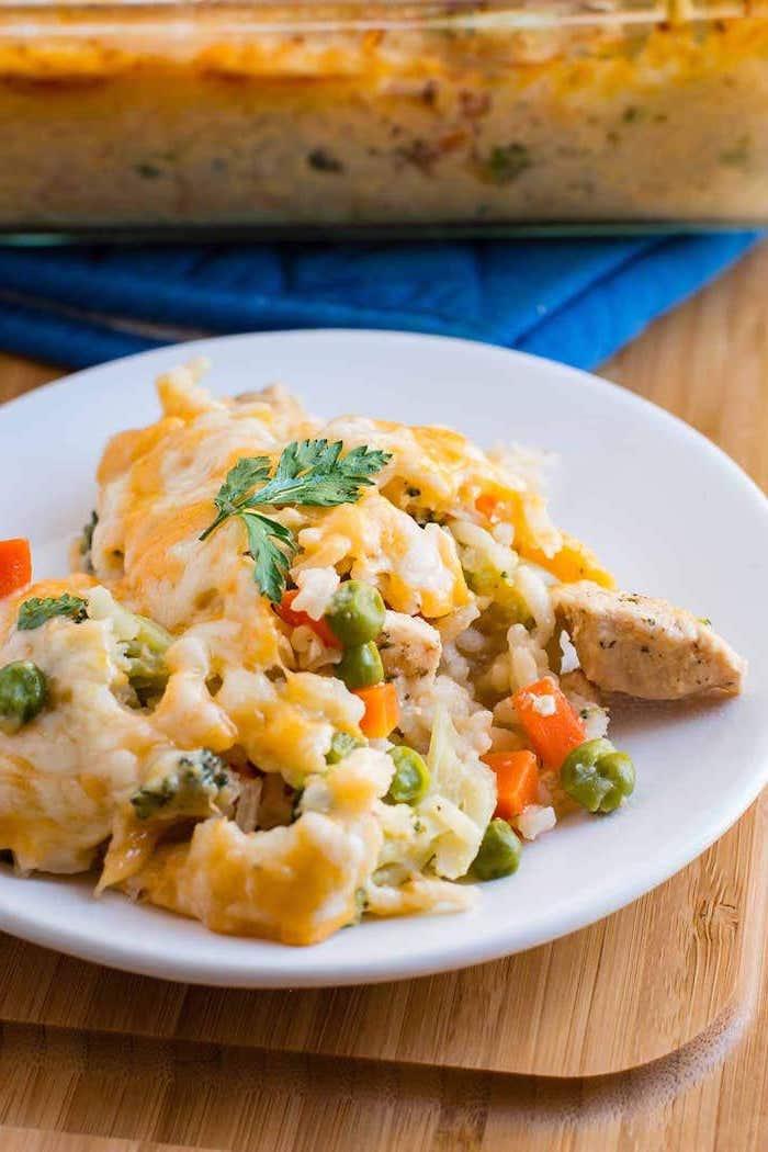 assiette blanche remplie de bouchées de poulet au riz, petits pois et carottes couvertes de fromage fondu, menu semaine