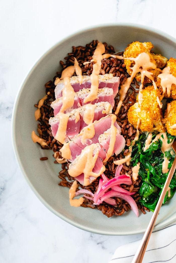 plat healthy consituté de thon, épinards, chou fleur frit sur canapé de riz brun dans assiette