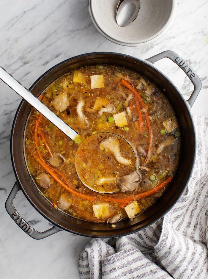 cocotte remplie de soupe aux champignons pleurotes avec des légumes et de la pate miso