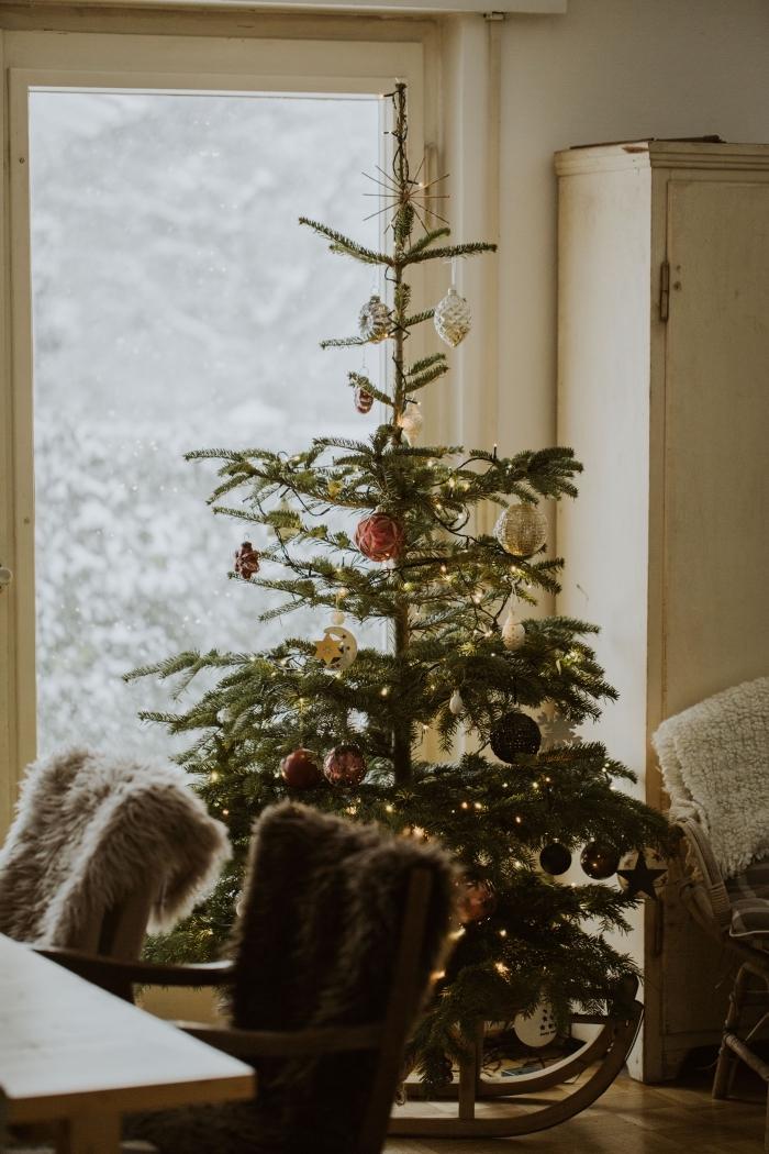 image noel 2019 avec un sapin naturel décoré d'ornements et guirlande lumineuse dans une salle de séjour avec chaise faux fur