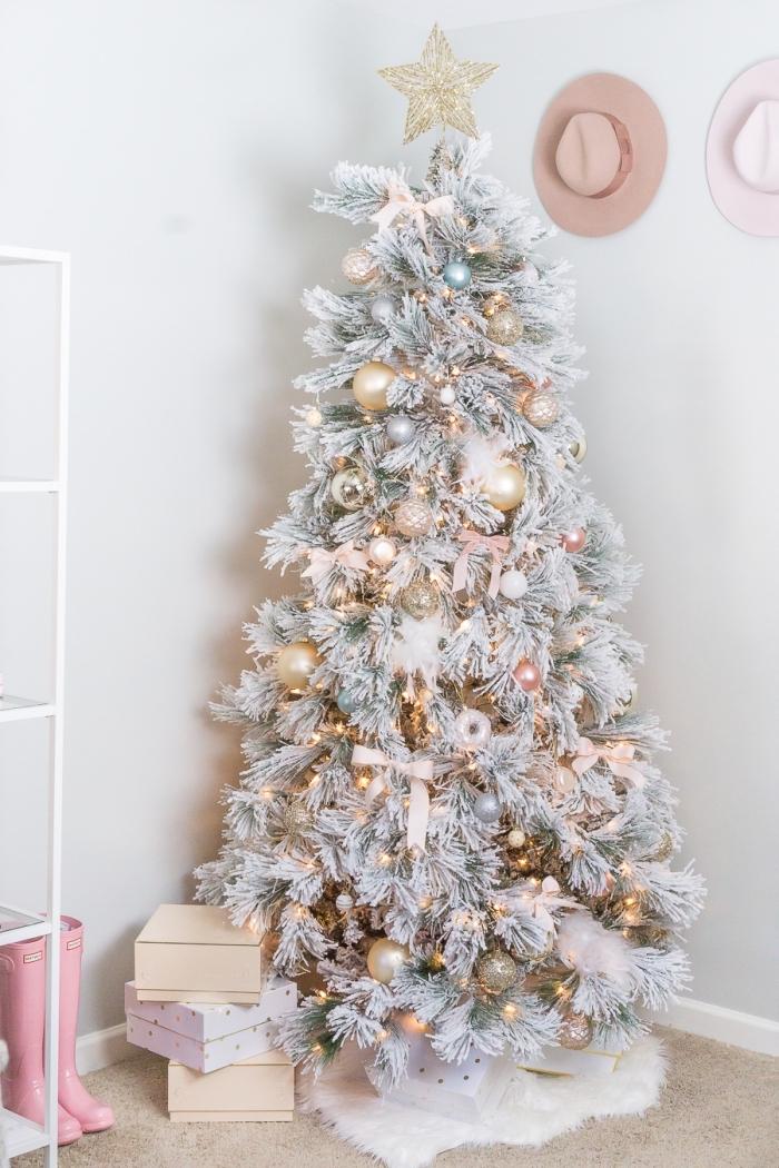 modèle de gros sapin artificiel aux branches blanches décoré avec boules dorées et ruban de couleur rose pâle