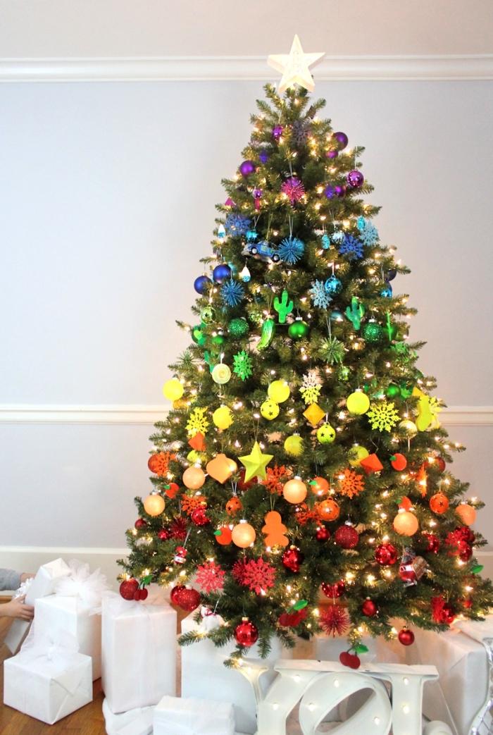 modèle arbre de Noël décoré à effet arc en ciel, image sapin de noel naturel décoré dans un salon aux murs blancs avec plancher bois foncé