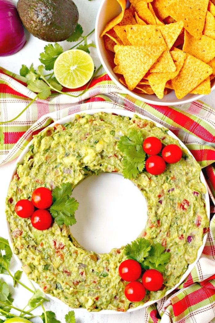 couronne de noel au guacamole mexicain décoré de tomates cerise et persil à servir avec chips tortilla, apero dinatoire original pour noel, dip maison