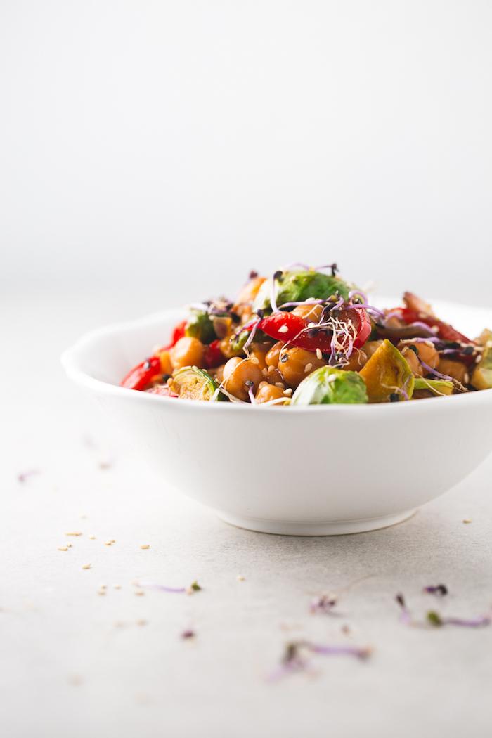 assiette blanche remplie d un plat équilibré, sauté de légumes aux pois chiche, choux de bruxelles et poivrons pour votre menu équilibré