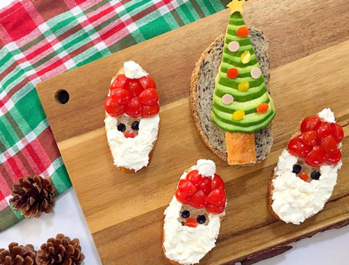 Pain décoré de fromage et tomates pour rassembler à père noël, amuse bouche apéritif facile, préparer un toast spécial pour la fête de noël