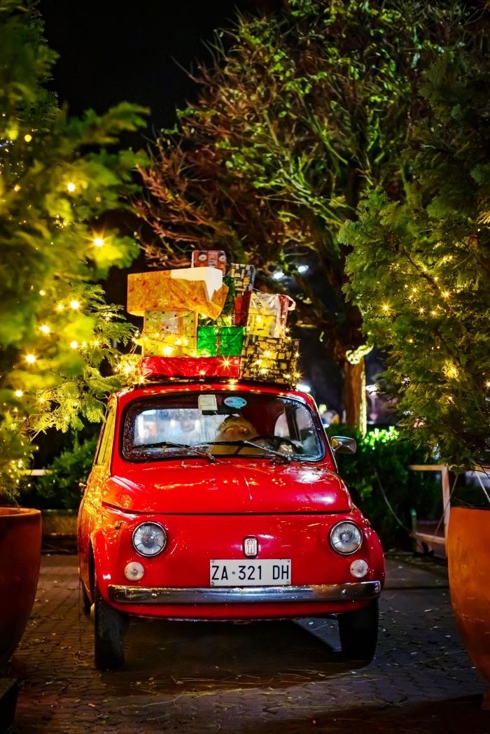 photo joyeux noel pour écran de verrouillage, idée photo de nuit avec lumières festives et mini voiture avec cadeaux de Noel, image de pere noel