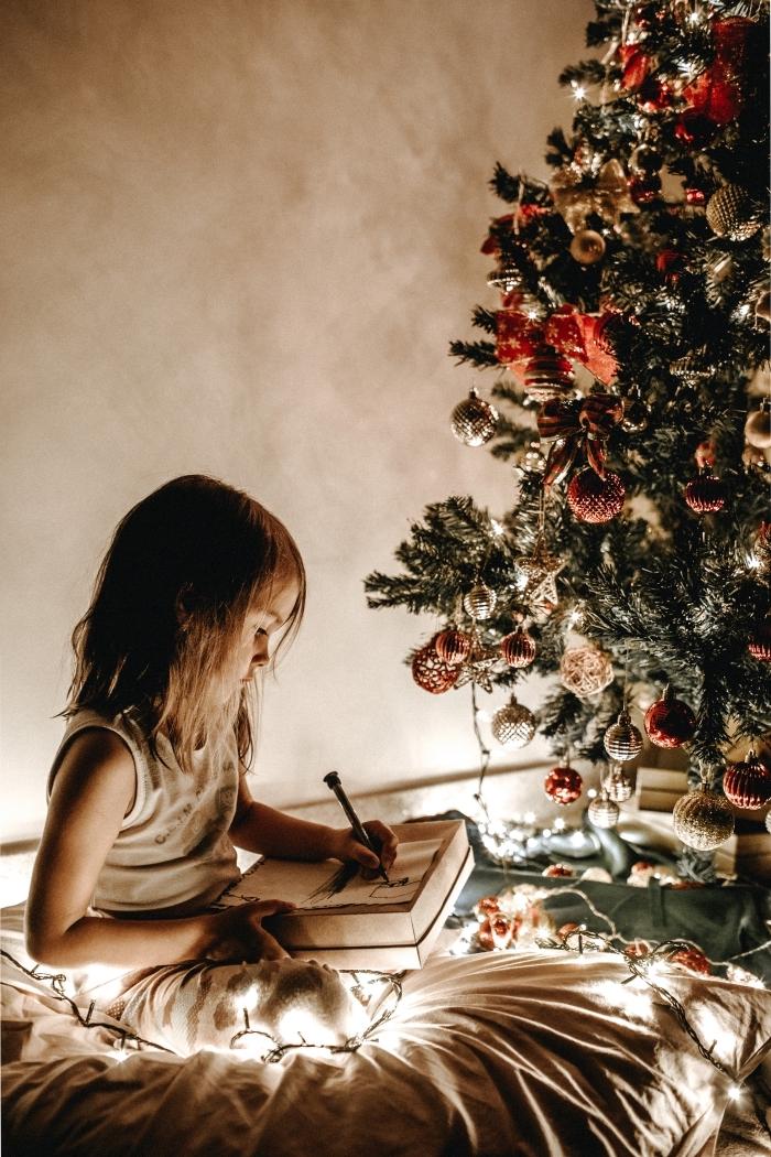 idée comment decorer un sapin avec ornements en rouge et or, photo de petite fille écrivant sa lettre au Père Noel