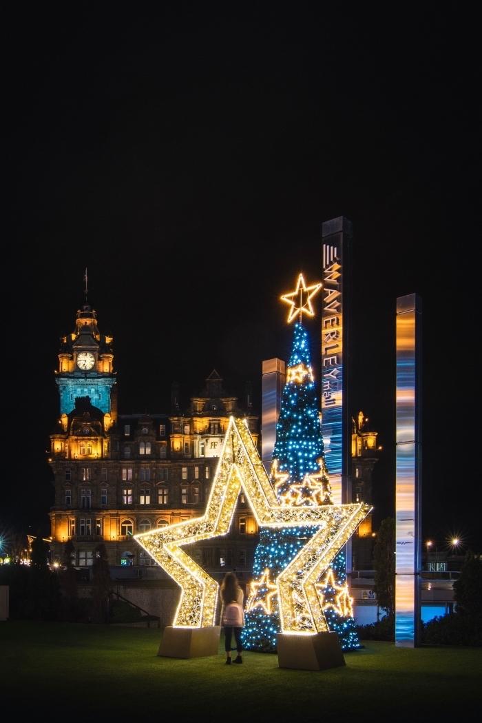 image de pere noel célébration pour fond d'écran portable, photo de nuit avec géant sapin et étoile lumineux