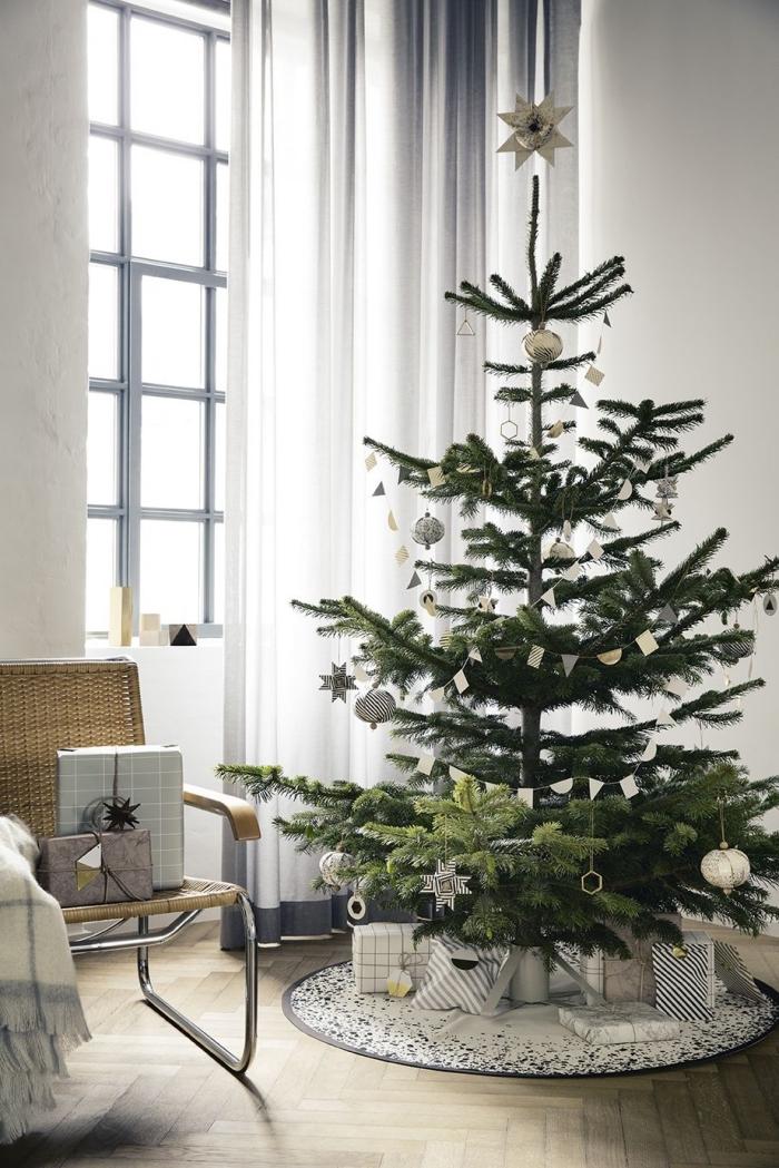 deco sapin noel minimaliste dans une pièce blanc et bois scandinave, arbre de noel décoré avec ornements métalliques
