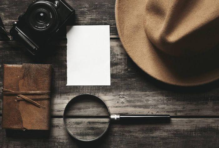 chapeau en couleur taupe, papier blanche, appareil photo noir en style vintage, livre avec couverture en cuir