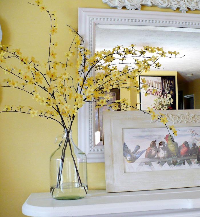 Branche fleurie aux jaunes fleurs, vase dame jeanne, composition florale à faire soi meme, vase de bouteille dame-jeanne, mur jaune