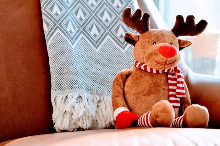 Cerf en pelouche sur le canapé, echarpe banc et gris, fond d écran image de joyeux noel, photo joyeux noel