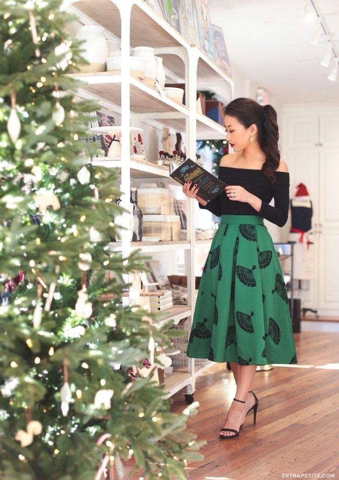 Belle femme tenue chic jupe mi longue et top épaules dénudées, s'habiller en vert et noir pour une photo auprès le sapin de Noël